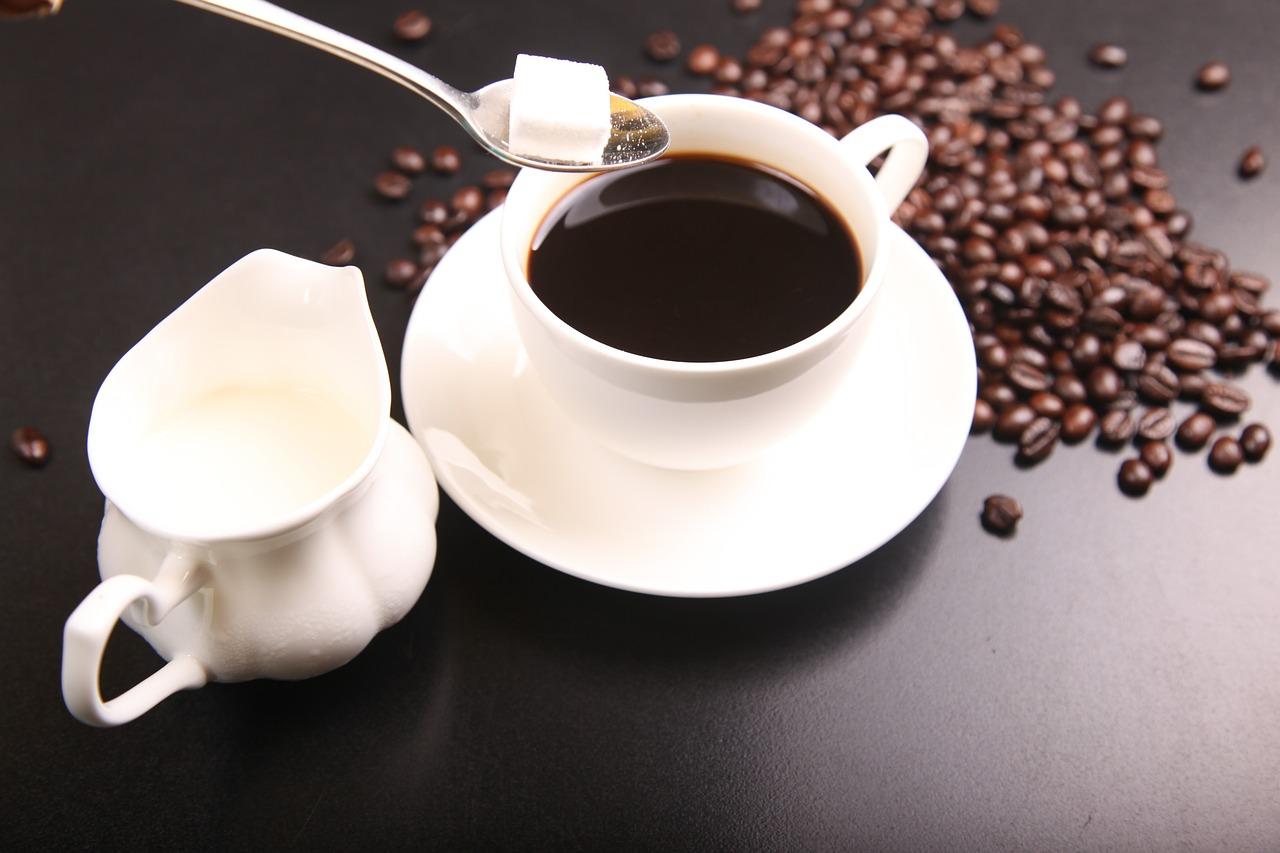 Coffee, sugar cubes, milk and coffee beans